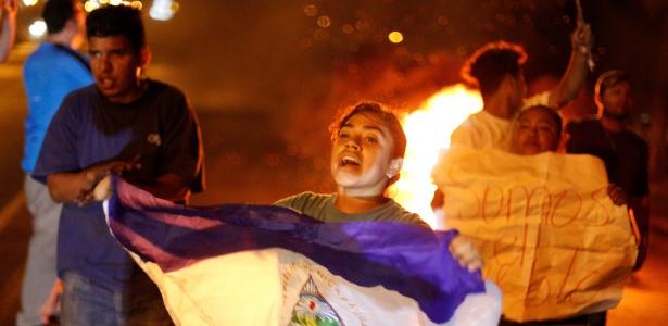 Manifestante empunha bandeira da Nicarágua em barricada durante protesto - Jorge Cabrera/Reuters