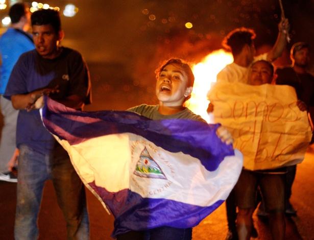 Manifestante empunha bandeira do país em protesto contra a Reforma da Previdência - Jorge Cabrera/Reuters