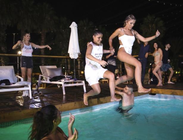 Shiran Abukasis, centro, salta em piscina durante sua festa de casamento, em Hadera - Corinna Kern/The New York Times