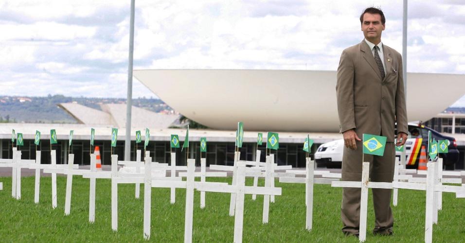 31.mar.2005 - O deputado Jair Bolsonaro posa entre cruzes em homenagem aos militares supostamente vitimados por terroristas durante o regime militar, fincadas em frente ao Congresso Nacional, em Brasília