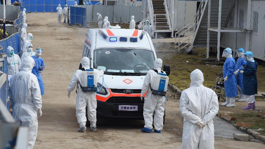 Agentes de saúde desinfetam ambulância que transporta pacientes com o novo coronavírus, em Wuhan, na China - Li Yun/Xinhua