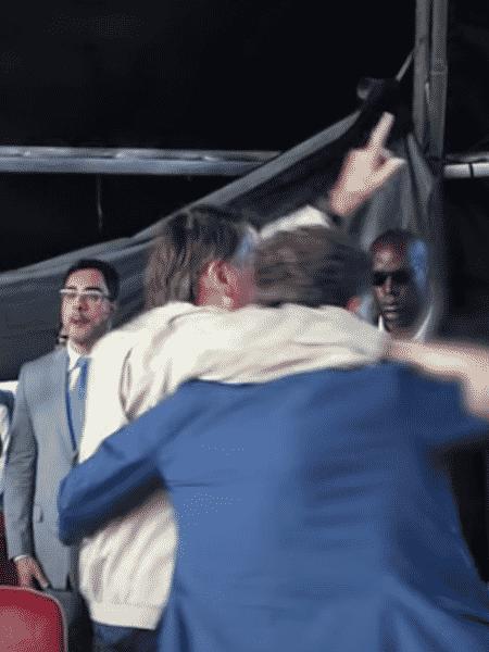 De costas, abraçados, Marcelo Crivella e Jair Bolsonaro. Ao fundo, Marcelo Bretas - Reprodução de vídeo