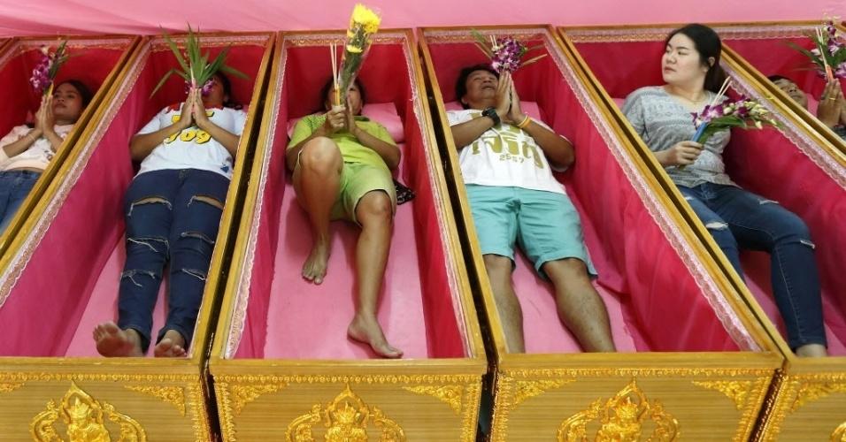 10.jan.2016 - Tailandeses religiosos participam de um ritual de ressurreição no templo budista Wat Takien, em Nonthaburi, nas imediações de Bancoc. No ritual, as pessoas ficam deitadas em caixões enquanto são cobertas por um pano. Monges cantam uma canção triste que simboliza a morte. Ao se levantarem, os fiéis sentem-se limpos de seus karmas, livres da má sorte e renascidos para um novo começo na vida com proteção, riqueza e boa saúde