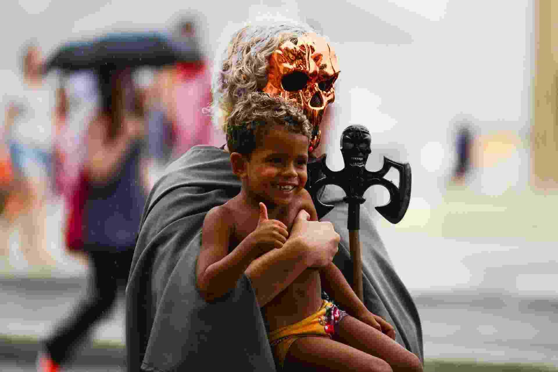 """17.jan.2016 - Homem fantasiado de diabo posa para foto com criança no colo, durante """"Marcha para Satanás"""", no Rio de Janeiro - Erbs Jr./FramePhoto/Estadão Conteúdo"""