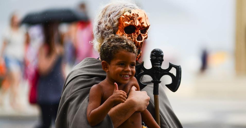 """17.jan.2016 - Homem fantasiado de diabo posa para foto com criança no colo, durante """"Marcha para Satanás"""", no Rio de Janeiro"""