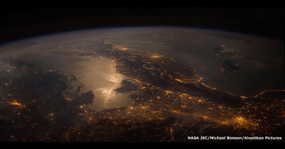 Os 77 trabalhos representam o que humanos veriam se fossem visitar esses lugares. Nesta imagem, Terra sendo vista a partir da Estação Espacial Internacional. A bota da Itália fica claramente visível. No canto inferior direito, as luzes são de Milão