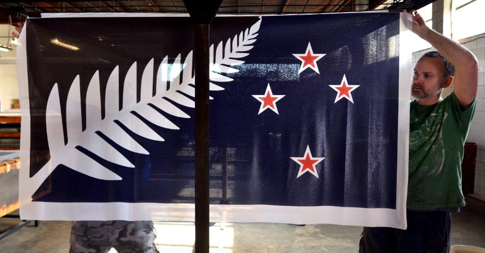 24.mar.2016 - Em imagem de arquivo, trabalhadores de fábrica em Auckland penduram bandeiras da Nova Zelândia com o novo desenho proposto e colocando em votação em um referendo. O resultado do referendo deve sair nesta quinta-feira, com resultados preliminares apontando para a manutenção da antiga bandeira do país, que remete à colonização britânica