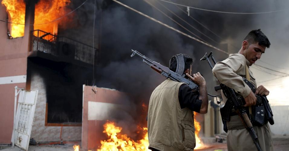 24.abr.2016 - Homens curdos armados seguram seus rifles em frente à casa em chamas de um militante xiita durante confrontos em Tuz Khurmato, no Iraque