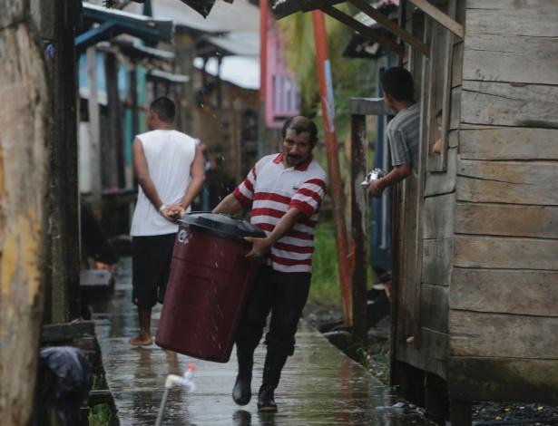 Homem carrega balde em bairro de Bluefields, na Nicarágua, antes da passagem do furacão Otto - Inti Ocon/AFP