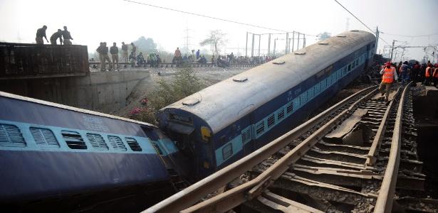 Funcionários e curiosos observam vagões de trem que descarrilou na Índia