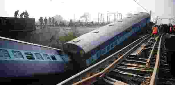 Funcionários e curiosos observam vagões de trem que descarrilou na Índia - Sanjay Kanojia/ AFP
