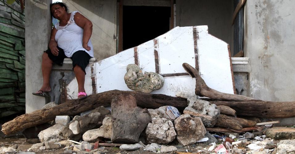 Moradora descansa um pouco durante os trabalhos de limpeza dos escombros de sua casa, após a passagem do Irma por Puerto Planta, na República Dominicana, na sexta-feira (8)