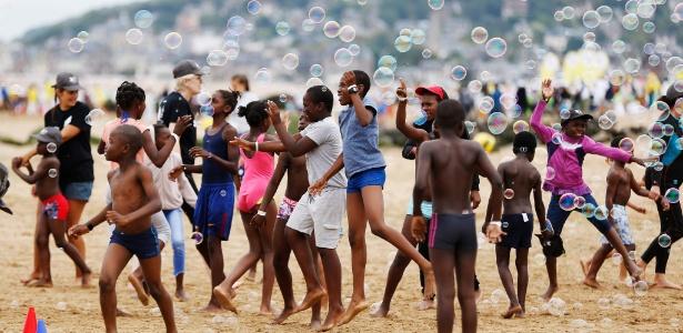 """Crianças brincam na praia de Cabourg, na Normandia, noroeste da França, durante a """"jornada dos sem-férias"""" - Charly Triballeau/AFP"""