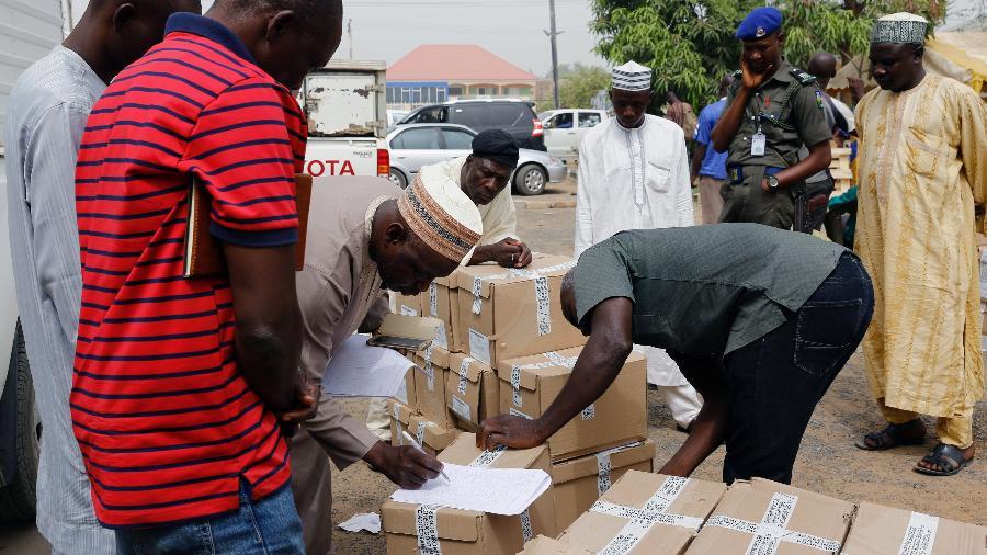 Funcionários marcam caixas com cédulas de votação antes de a eleição presidencial ser adiada na Nigéria - Nyancho NwaNri/Reuters