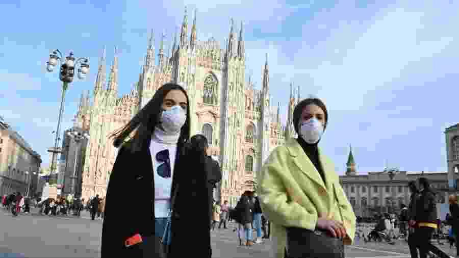 Mulheres usam máscara no rosto na Piazza del Duomo, no centro de Milão - Andreas Solaro/AFP