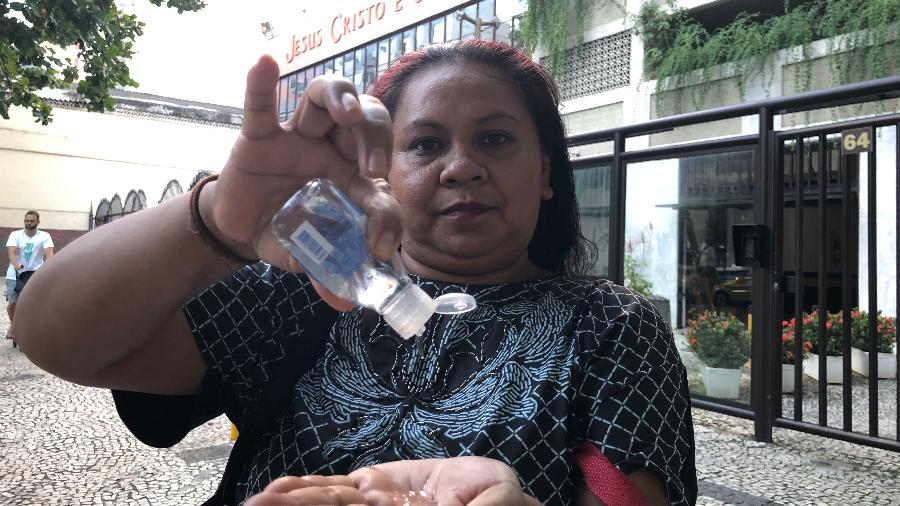 26.mar.2020 - A atendente de supermercado Celma Miranda, que leva álcool em gel na bolsa, deixa templo após oração - Herculano Barreto Filho/UOL