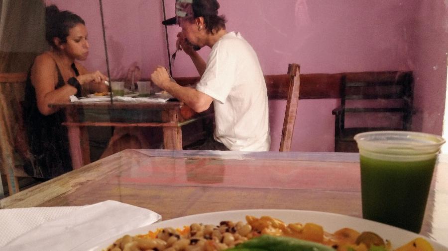 Amigos almoçam no restaurante Green Chef, em São Paulo, separados por divisória de plástico - Marcelo Oliveira/UOL