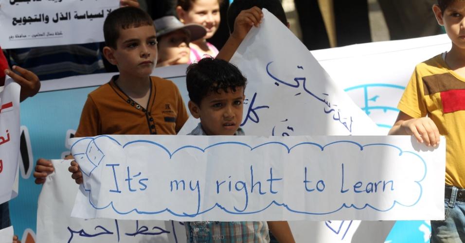 15.ago.2015 - Garoto palestino segura uma faixa em que se lê