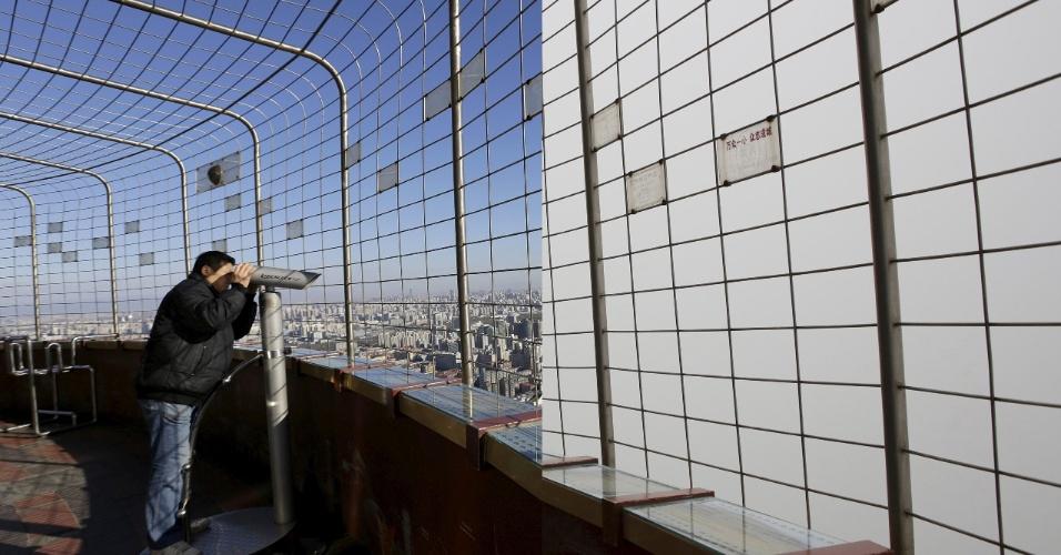Deck de observação da cidade de Pequim ficou praticamente inútil em dia de poluição. Quando o ar está limpo, como na foto tirada em 2 de dezembro, é possível ver praticamente toda a cidade. Já com a neblina de 2 de dezembro é quase impossível enxergar algo