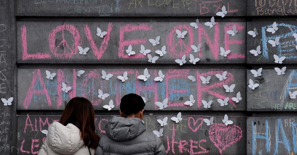 """24.mar.2016 - Casal observa mensagem em inglês que diz """"Amem uns aos outros"""" deixada no muro de uma praça na região central de Bruxelas. Nesta semana, a capital belga e sede da União Européia foi alvo de dois ataques terroristas coordenados que deixaram mais de 30 mortos e cerca de 300 feridos"""