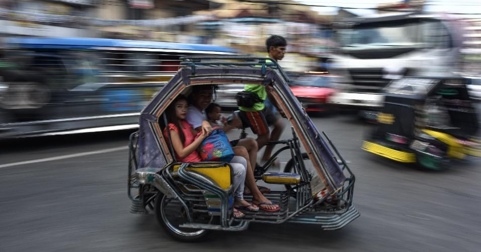 7.mai.2016 - Família filipina circula por Manila em tradicional táxi triciclo antes de início de eleições presidenciais no país. Rodrigo Duterte, advogado em casos de homicídio em massa, chega ao final da campanha como favorito, mas com os rivais ainda com chances de combater suas propostas consideradas populistas
