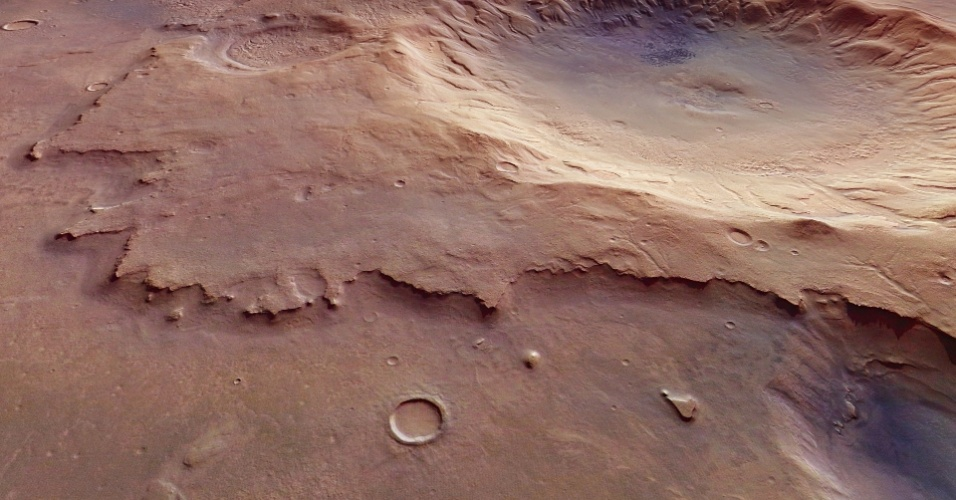 18.jul.2016 - A nave espacial Mars Express da ESA (Agência Espacial Europeia) fotografou uma cratera no solo de Marte. A cratera, visível no canto superior direito da imagem, tem cerca de 4 km de profundidade e 50 km de diâmetro. A região fotografada fica ao sudoeste do planeta, em uma planície chamada de Mare Serpentis, o mar de serpentes