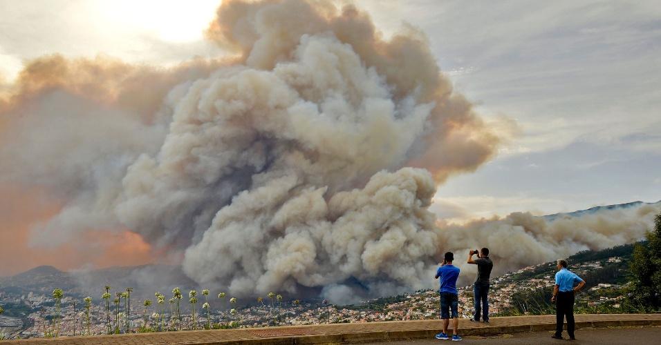 9.ago.2016 - Curiosos tiram foto de fumaça em Curral dos Romeiros, na Ilha da Madeira, em Portugal. Várias casas foram destruídas pelas múltiplas chamas oriundas de incêndio florestal e mais de 250 pessoas foram evacuadas de suas casas para passar a noite em instalações militares, segundo o governo local