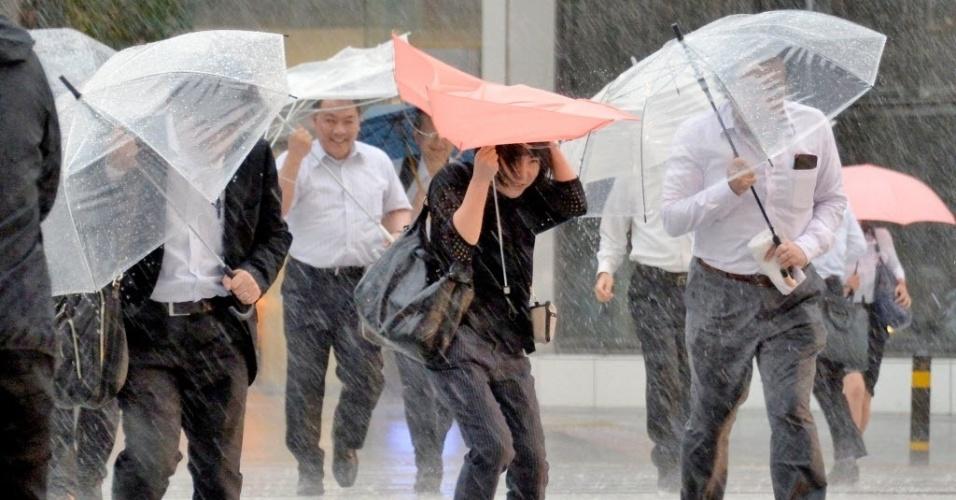 20.set.2016 - Pedestres enfrentam forte chuva provocada pela chagada do tufão Malakas em Nagoya, no Japão