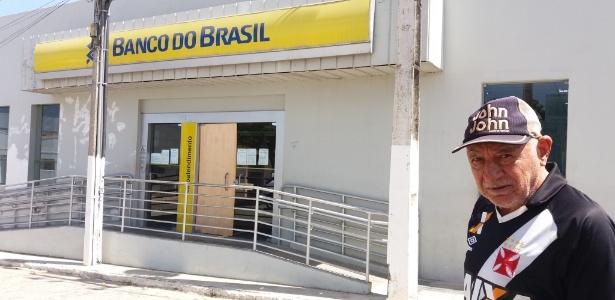 O aposentado João Rosendo diante de agência que teve a entrada explodida em Barra de Santa Rosa (PB)
