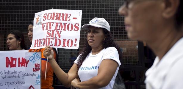 Mulher segura cartaz que critica a falta de medicamentos na Venezuela