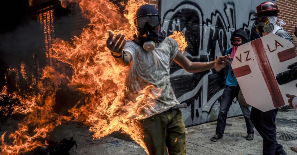"""3.mai.2017 - O estudante Victor Salazar, 28, saiu gritando em uma bola de fogo, depois que uma motocicleta da polícia que os manifestantes estavam destruindo explodiu. O fotógrafo Juan Barreto estava a alguns metros. """"O cara estava correndo na minha direção, coberto em chamas. Eu não podia fazer nada para ajudá-lo"""", disse Barreto. Da cama de hospital onde ficou internado, com queimaduras em 70% do corpo, Salazar mandou um vídeo para os manifestantes: """"Vão para as ruas, não por mim, mas pela Venezuela""""."""