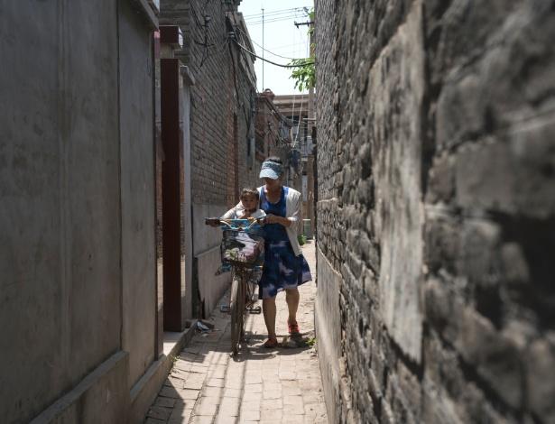 4.jun.2017 - Mãe empurra filho por viela estreita no vilarejo histórico de Quantou, na China - Sim Chi Yin/The New York Times
