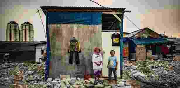 11.nov.2017 - Asmawati e seu filho, Topaz, nas ruínas do bar Akuarium, em Jacarta, na Indonésia - Josh Haner/The New York Times - Josh Haner/The New York Times