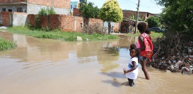 Com o filho de seis meses no colo, Luana Conceição leva menina de quatro anos à escola em rua alagada em Guaratiba, zona oeste do Rio de Janeiro - Fabiano Rocha/Agência O Globo