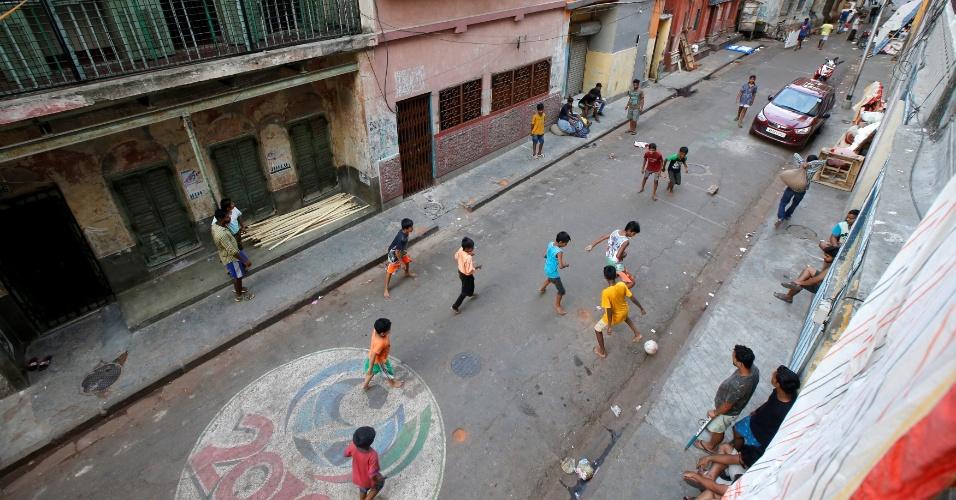 12.maio.2018 - Garotos jogam futebol descalços em Calcutá, na Índia