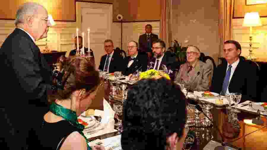 Ao lado de Olavo de Carvalho, presidente Jair Bolsonaro acompanha o discurso do embaixador brasileiro nos EUA, Sérgio Amaral - lan Santos/PR