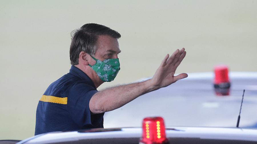 Presidente Jair Bolsonaro, usando máscara do Palmeiras, acena para simpatizantes na porta do Palácio da Alvorada - Dida Sampaio/Estadão Conteúdo