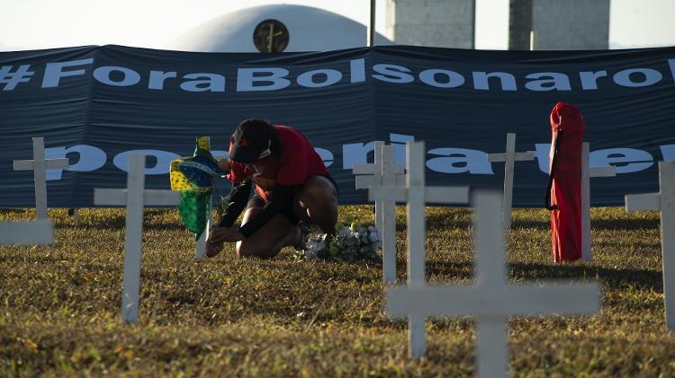 Homem posiciona cruz e flor para representar vítima do coronavírus em ato em Brasília - MATHEUS W ALVES/FUTURA PRESS/ESTADÃO CONTEÚDO - MATHEUS W ALVES/FUTURA PRESS/ESTADÃO CONTEÚDO