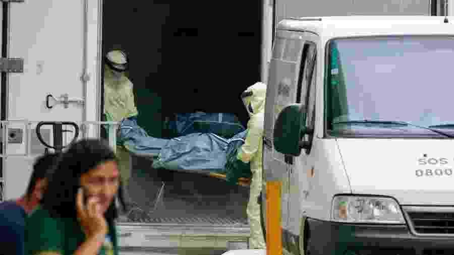 04.jan.2021- Funcionários do Hospital Pronto-Socorro João Lúcio retiram corpo de vítima da covid-19 de contêiner frigorífico, em Manaus - SANDRO PEREIRA/ESTADÃO CONTEÚDO