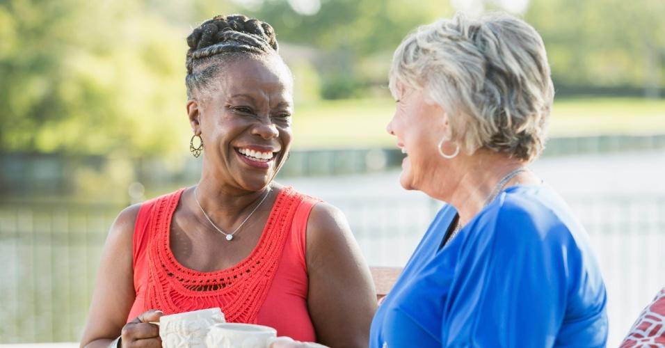 Duas mulheres, uma vestida de vermelho e outra de azul, conversam amigavelmente
