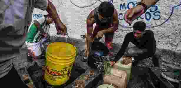 27.mai.2016 - Homens enchem galões com água de poço em Caracas, na Venezuela - Meridith Kohut/The New York Times - Meridith Kohut/The New York Times