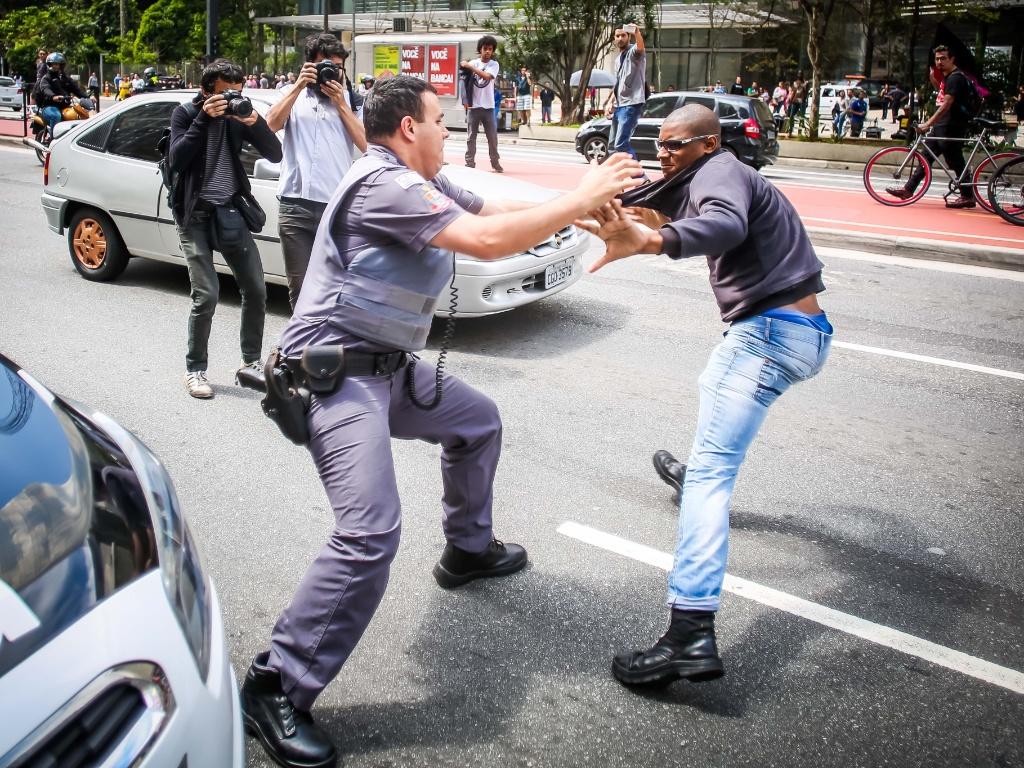 29.out.2016 - Policial tenta conter manifestante durante ato na avenida Paulista, em São Paulo. Manifestação neste sábado reuniu grupo a favor do candidato republicano Donald Trump nas eleições presidenciais dos EUA