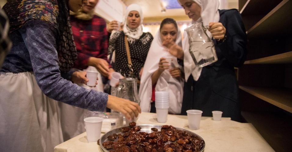 7.jun.2017 - Mulheres encerram o jejum com água e tâmaras secas, logo após o pôr do sol, durante o Ramadã