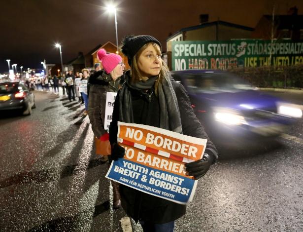 Manifestantes protestam em uma estrada com cartazes anti-Brexit, no oeste de Belfast, na Irlanda - PAUL FAITH/AFP