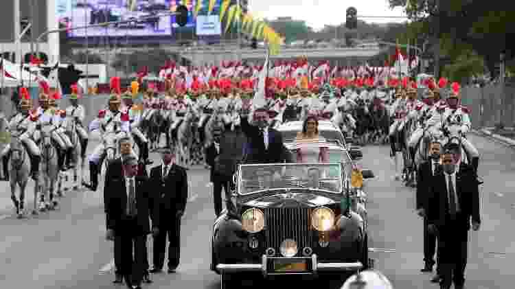 Bolsonaro acompanhado da primeira-dama, Michelle, e de um dos filhos, Carlos, desfila em carro aberto - Gabriela Biló/Estadão Conteúdo