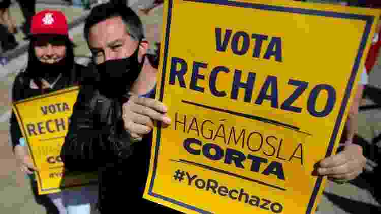 Casal segura cartaz afirmando: 'Vote rejeito; vamos encurtar (o processo)' - Getty Images - Getty Images