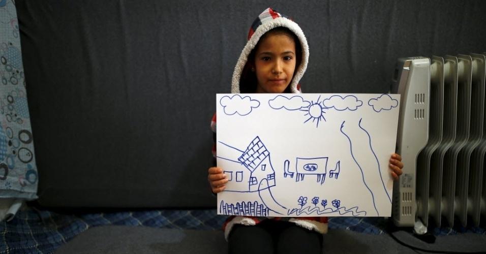 Refugiada síria Hale Selim, 13, mostra desenho de sua casa na Síria. Atualmente ela vive no campo de refugiados de Yayladagi, na província de Hatay, na Turquia, perto da fronteira com Síria. A guerra civil na Síria, que já deixou centenas de milhares de mortos, empurra outros tantos para o exílio, entre muitos deles crianças. Os desenhos das crianças do acampamento mostram memórias de suas casas, traumas vividos e esperanças para o seu futuro. Dos 2,3 milhões de refugiados sírios que vivem na Turquia, mais da metade são crianças
