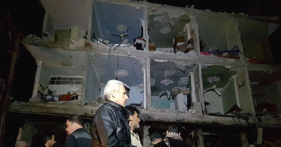 21.fev.2016 - Sírios caminham por área destruída em Damasco após o atentado terrorista que deixou mais de 50 mortos na capital do país. O Estado Islâmico assumiu a autoria de três ataques a bomba em um reduto xiita no bairro de Sayyida Zeinab.
