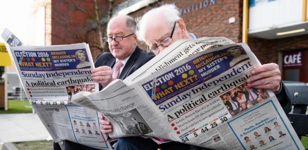 Membros do Fianna Fail leem jornais com noticiário sobre as eleições em Dublin (Irlanda)
