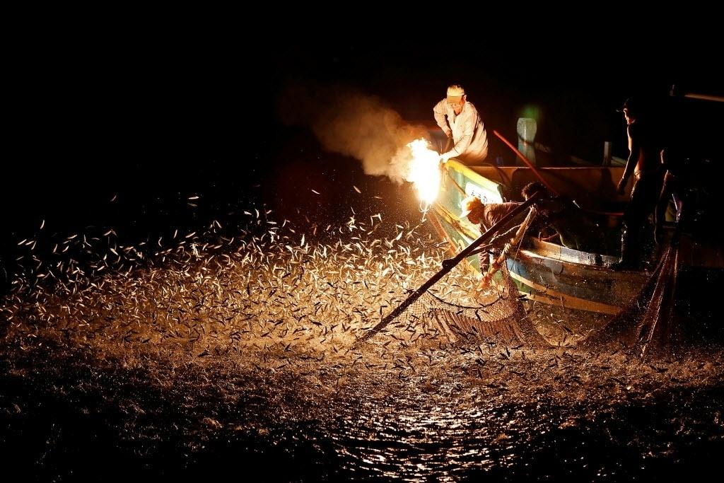 27.jun.2016 - Pescadores usam chamas para atrair peixes em Nova Taipé, Taiwan. Os homens usam um método ancestral e sustentável de pesca em que eles misturam água e enxofre para obter acetileno e produzir luzes que atraem pequenos peixes prateados para fora d'água